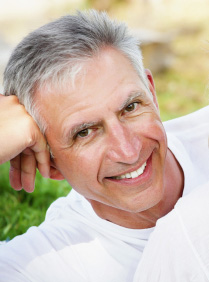 Smiling older man from East Lake, FL shows off his new porcelain crowns and dental bridges.